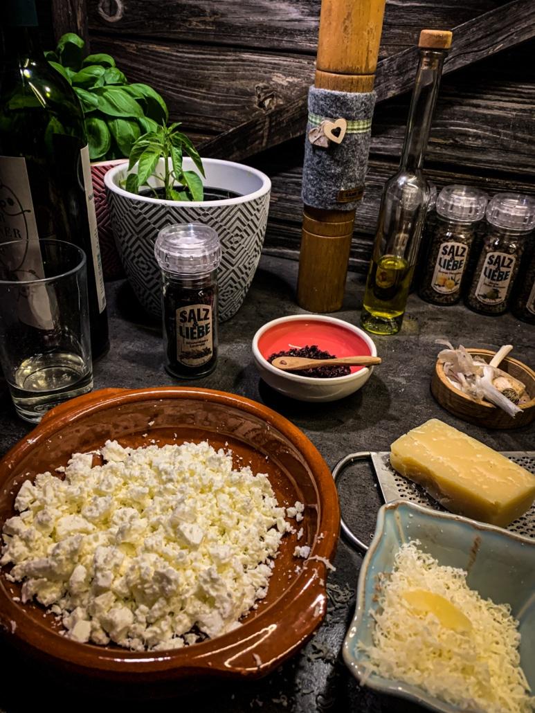 Schafskäse und Parmesan reiben.